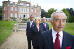 Businessman by colleagues in grounds of manor house, portrait Stock Image