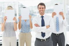 Businessman with colleagues holding blank paper in front of faces Stock Image