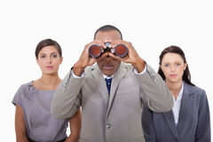 Businessman with colleagues using binoculars Royalty Free Stock Image