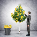 Businessman collecting dollar signs from tree Stock Photo