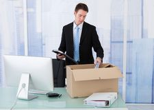 Businessman collecting office supply in cardboard box at desk Stock Photography