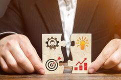 Businessman collects puzzles with the image of the attributes of doing business. Strategy planning concept. Organization of the. Process. Creating a business stock image