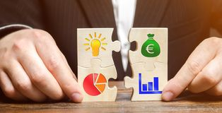 Businessman collects puzzles with the image of the attributes of doing business. Strategy planning concept. Organization of the. Process. Creating a business stock photography