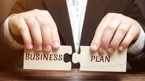 Businessman collects puzzles with the word Business Plan. Business operations program. Organization and management of processes stock photography