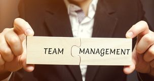 Businessman collects puzzles with the words Team management. Increase efficiency. Hiring and dismissal employees. Organization of. Working business process stock photography
