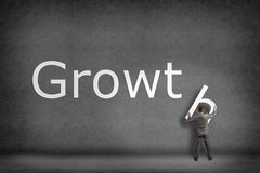 Businessman collects on the wall the word growth Stock Photo
