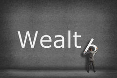 Businessman collects on the wall the word wealth Royalty Free Stock Images