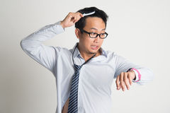 Businessman combing hair in morning in hurry. Asian businessman combing hair in morning in hurry, checking time on watch, on plain background Stock Image