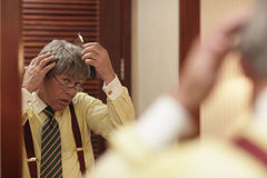 Businessman combing his hair stock photo