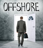 Businessman comes in door with word offshore Stock Image