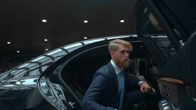 Businessman comes out of a executive car, top manager comes to the important meet, famous rich man comes out of his car. With personal driver, business class stock footage