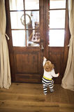 Businessman coming home, little son at the door welcoming him. Stock Photos