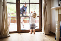 Businessman coming home, little son at the door welcoming him. Royalty Free Stock Photos