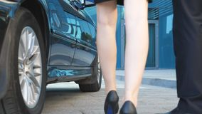 Businessman coming to car and opens door for young woman. Man uncover door of automobile for female passenger. Businesswoman get out from the auto and leaves stock footage