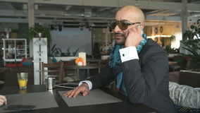 Businessman communicates on a smartphone. Businessman of Arab origin communicates on a smartphone at the restaurant airport stock video footage