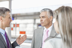 Businessman communicating with colleagues on railroad platform Royalty Free Stock Photos