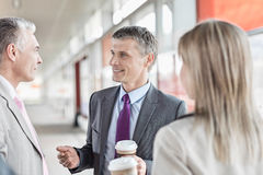 Businessman communicating with colleagues on railroad platform Royalty Free Stock Image