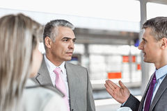 Businessman communicating with colleagues on railroad platform Stock Images