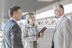Businessman communicating with colleagues on train platform Stock Image