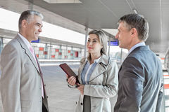 Businessman communicating with colleagues on train platform Royalty Free Stock Images