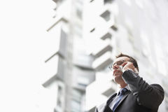 Businessman Communicating On Mobile Phone Against Tall Building Royalty Free Stock Photo