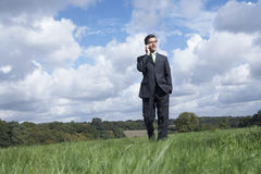 Businessman Communicating On Mobile Phone In Field Stock Image