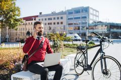 Businessman commuter with electric bicycle sitting on bench, using laptop and smartphone. Hipster businessman commuter with electric bicycle sitting on bench royalty free stock image