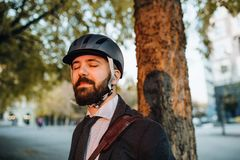 Businessman commuter with helmet standing in city at sunset, eyes closed. Copy space stock image