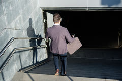 Businessman commuter traveling and going down the metro Stock Photos