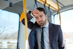 Businessman commuter is traveling and he is sad and tired. Businessman commuter is traveling and is sad and tired royalty free stock image