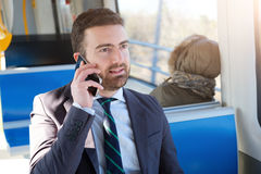 Businessman commuter is traveling and is talking Stock Photo