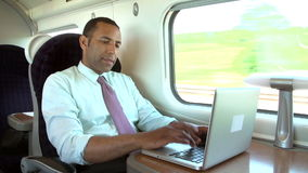 Businessman Commuting To Work On Train And Using Laptop. Businessman sitting at table working at laptop.Shot on Sony FS700 in PAL format at a frame rate of 25fps stock footage