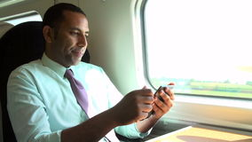 Businessman Commuting On Train Reading E Book. Businessman sitting at table looking at e-reader.Shot on Sony FS700 in PAL format at a frame rate of 25fps stock footage