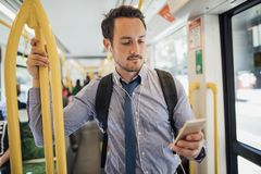 Businessman Commuting By Tram In Melbourne. Millennial businessman is commuting on a tram in Melbourne, Victoria. He is watching something on his smart phone royalty free stock photos