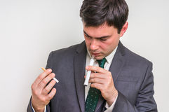 Businessman is comparing electronic cigarette and tobacco cigare. Businessman in suit is comparing electronic cigarette and tobacco cigarette Stock Photo