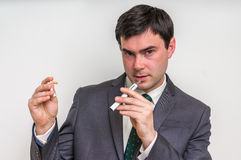 Businessman is comparing electronic cigarette and tobacco cigare. Businessman in suit is comparing electronic cigarette and tobacco cigarette Royalty Free Stock Photo