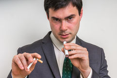 Businessman is comparing electronic cigarette and tobacco cigare. Businessman in suit is comparing electronic cigarette and tobacco cigarette Stock Images