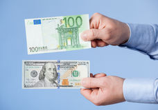 Businessman comparing hundred dollars and hundred euro Stock Photos