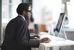 Businessman by computer Royalty Free Stock Images