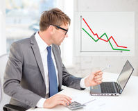 Businessman with computer, papers and calculator Royalty Free Stock Photo