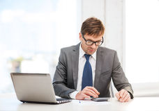 Businessman with computer, papers and calculator Royalty Free Stock Image