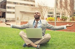 Businessman with computer relaxing outside corporate office Royalty Free Stock Images