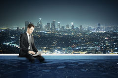 Businessman with computer in rooftop pool Stock Photos