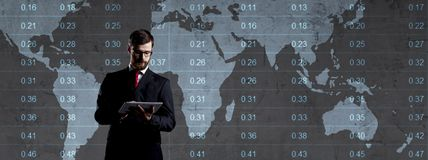 Businessman over dark background. World map background. Business, globalization, capitalism concept. Businessman with computer tablet standing over diagram stock photos