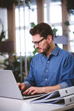 Businessman concentrating on laptop at creative office royalty free stock photos