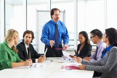 Businessman Conducting Meeting In Boardroom Stock Photo
