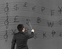 Businessman conducting with money symbols stave on wall Royalty Free Stock Images