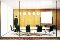 Businessman in conference room. Thoughtful young businessman in modern conference roon with blank whiteboard. Mock up, 3D Rendering Royalty Free Stock Photography