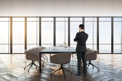 Businessman in conference room. Thoughtful young businessman standing in modern conference room interior with city view, daylight and furniture stock images