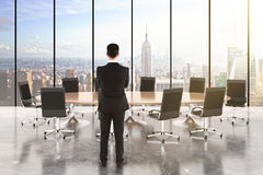 Businessman in a conference room with wooden table and chairs Stock Photos